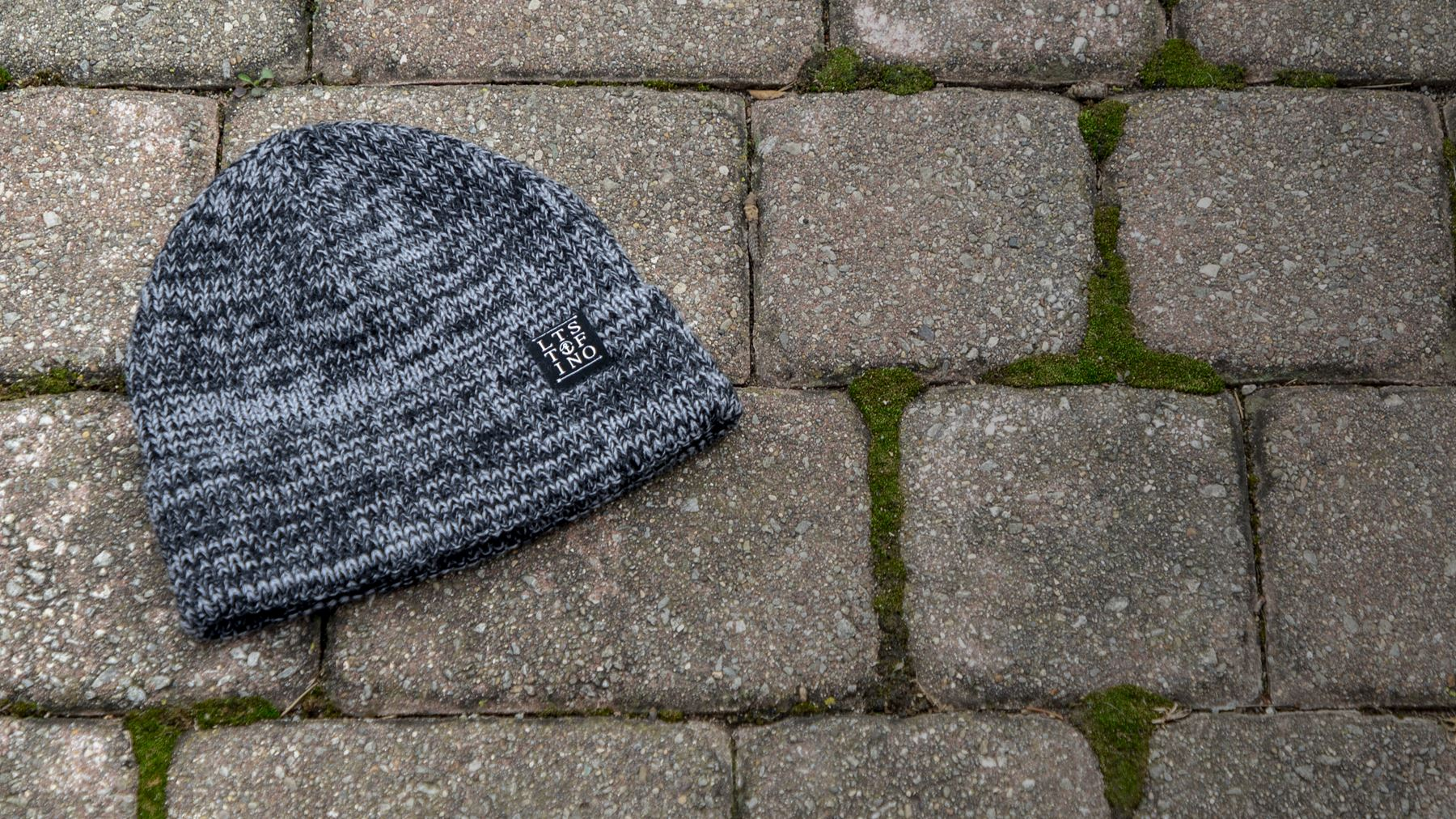 Woodberry knit hat laying on stone path