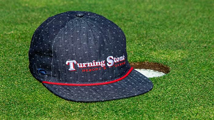 Tour hat by a golf hole