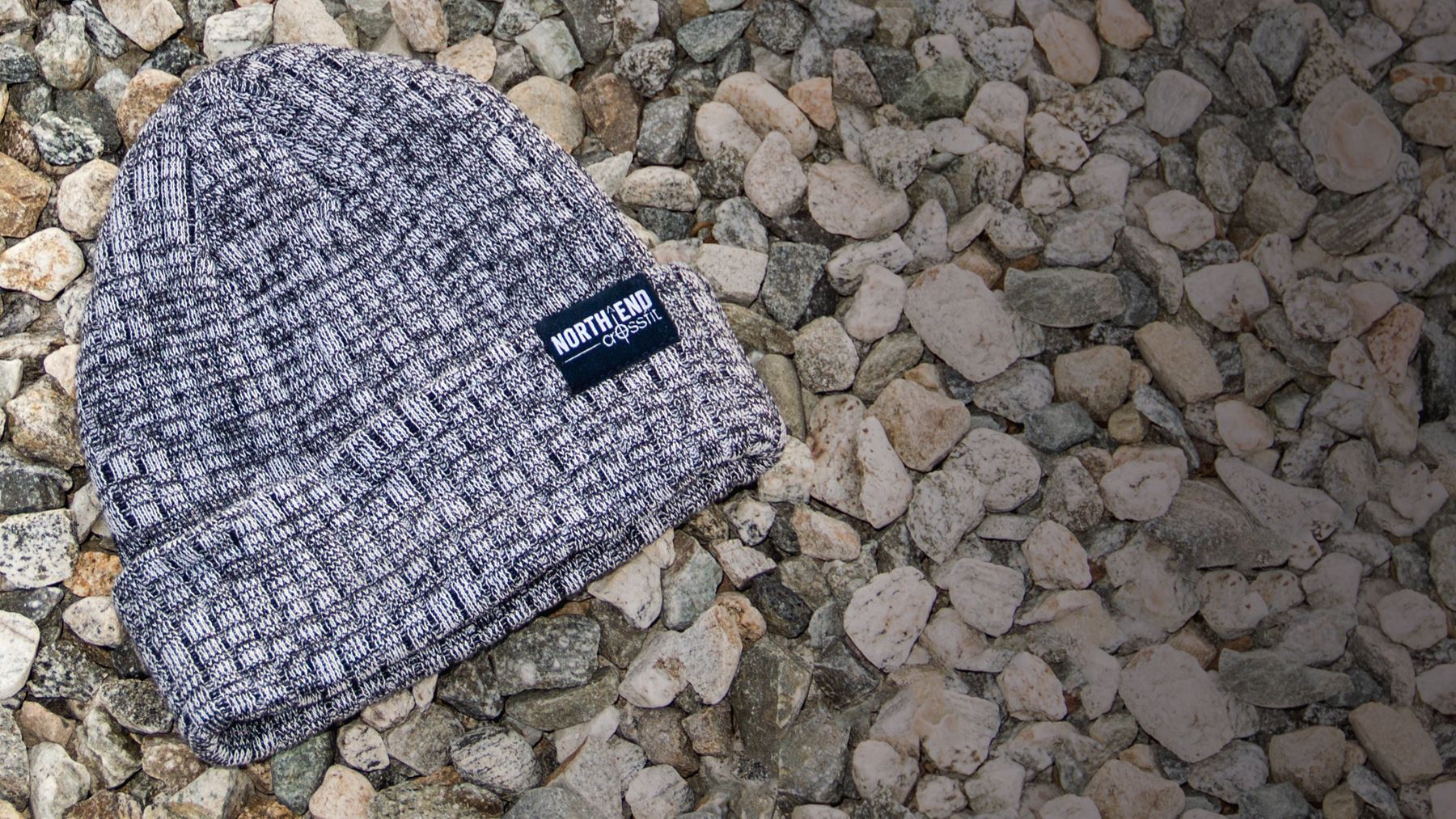 Belafonte knit hat laying on a bed of small stones